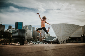 Happy woman jumping in the air in Sydney, with the cityscape in the background. Australia.