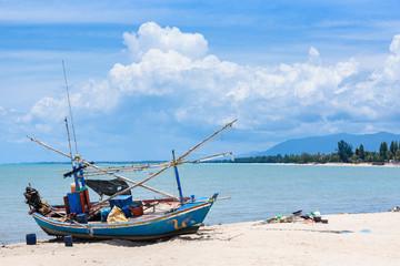Fishing boats aground on the beach over cloudy sky at Prachuap Khiri Khan, Thailand.