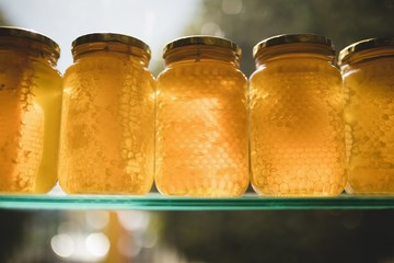 Honey and comb in glass jars on shelf