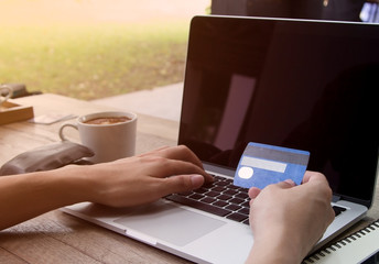 man shopping online wiht credit card and entering infometion on keyboard
