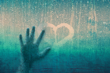 Grunge cracked human hand on droplet rainy glass window with love heart symbol. Conceptual love breakup image.