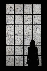 Lonely woman looking through big cracked window and thinking about things. Conceptual lonely or sad women silhouette background.