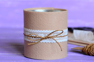 Decorated tin can crafts. Simple and cheap way for beautiful decorating old tin can. Recycled craft idea. Materials and tools for creative work on a wooden table. Closeup