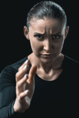 portrait of young fitness woman stretching hand isolated on black