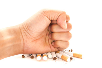 Close-up man hand crushing a pile of cigarettes isolated on white. Angry hand breaking tobacco. Gesture for anti, quit smoking addiction concept. Stop smoking message, social issue concept background.