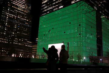 Visitors to the National September 11 Memorial and Museum stand in front of One World Trade Center, which was lit green for Saint Patrick's day, in Manhattan, New York, U.S.