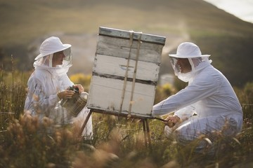 Male and female beekeepers working on beehive at field