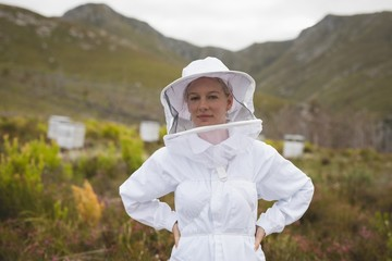 Confident apiarist wearing bee suit at apiary