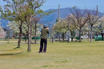 公園で携帯電話で写真を撮る老人