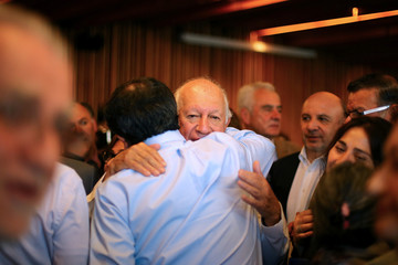 Former Chile's president and center-left presidential candidate Ricardo Lagos is hugged after dropping out his presidential campaign, in Santiago