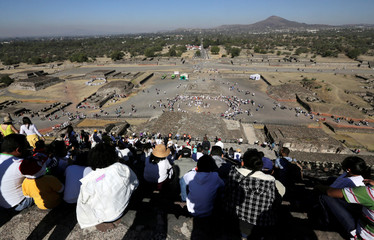 People wait to welcome the spring equinox while standing on the Pyramid of the Sun in the pre-hispanic city of Teotihuacan, on the outskirts of Mexico City