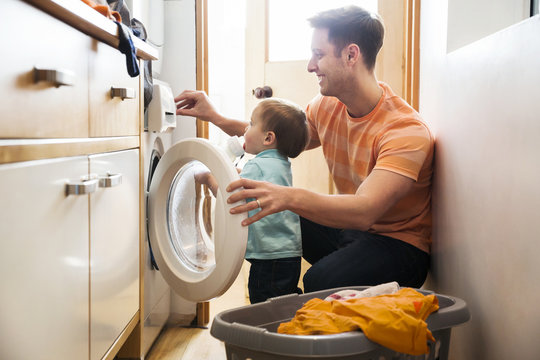 Father and toddler son doing laundry at home