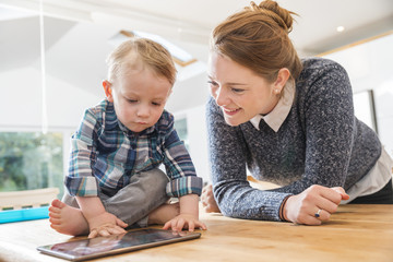 mother and toddler son looking at tablet at home