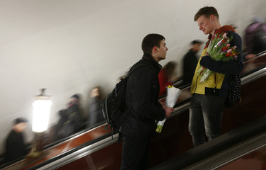 Men hold bunches of flowers as they use escalator at Rizhskaya metro station in Moscow