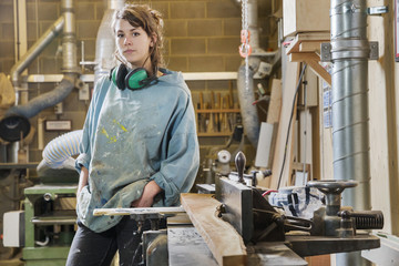 Portrait of young woman next to machinery in wood workshop