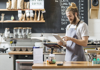 young man behind a counter in a cafe using a tablet