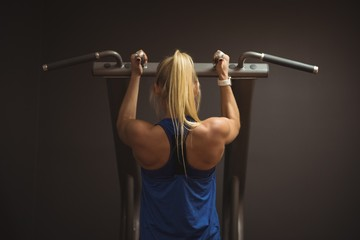 Rear view of fit woman exercising on a machine