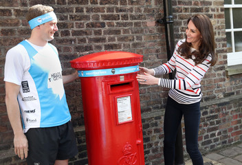 Britain's Catherine, Duchess of Cambridge poses for a photograph with runner Alex Stanley at Kensington Palace, in London