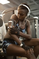 Young woman listening music at gym