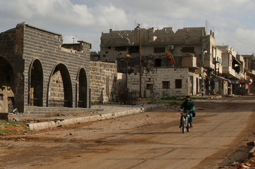 A man drives a motorcycle near damaged Omari Mosque in the southern old city of Deraa