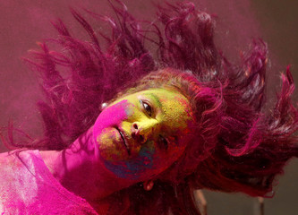 A woman smeared with coloured powder shakes her head while celebrating Holi, the Festival of Colours, in Mumbai
