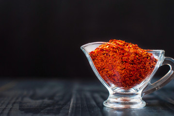 Chile pieces in a glass jar. Red ground chili on a dark background.
