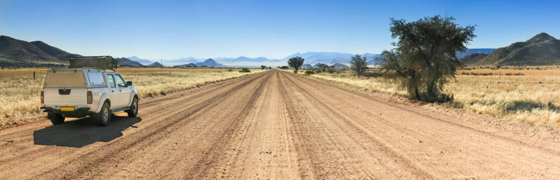 Pickup truck driving fast on long straight desert road