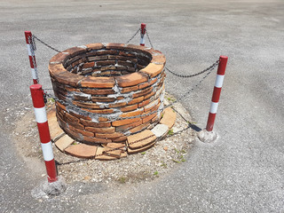 old well on the road with chain and red white sign around