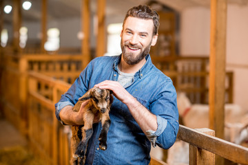 Handsome farmer taking care of cute goat baby at the barn