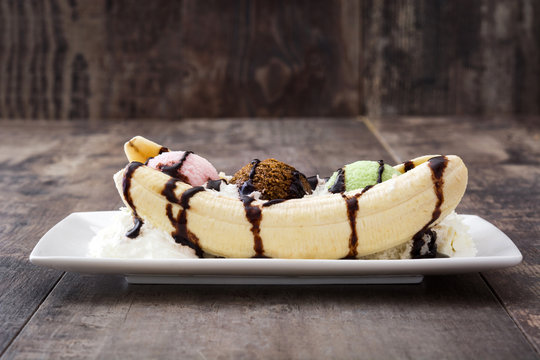 Banana split ice cream dessert with chocolate syrup on wooden background