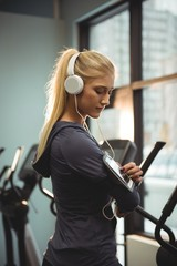 Fit woman using smartphone in armband