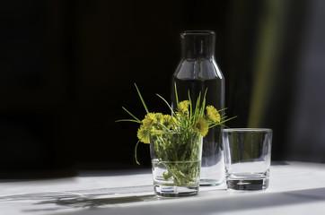 Весенние одуванчики на столе в стакане вместе со стеклянной посудой