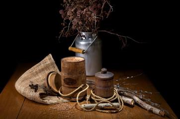 Натюрморт из деревянных банок с гречневой крупой, тканью, березовых палочек, железного бидона и веревки