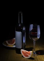 Бутылка и бокал с красным вино и фруктами