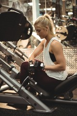 Fit woman using smartwatch on a machine