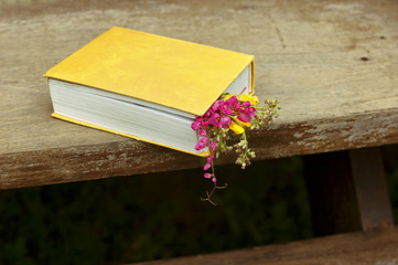 Closed book with flowers on wood table background