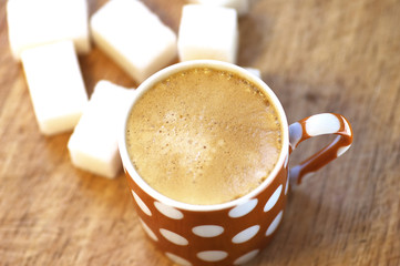 Cup of coffee and sugar cubes on wooden board