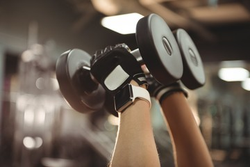 Hands of fit woman exercising with dumbbells