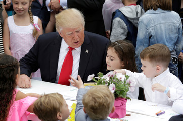 U.S. President Donald Trump speaks with children as they make Easter greeting cards for members of the military at the 139th annual White House Easter Egg Roll on the South Lawn of the White House in Washington