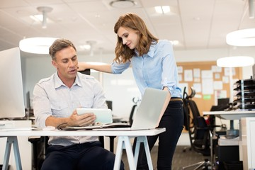Businessman discussing with female colleague in office