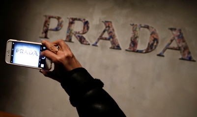 A guest takes a picture of Prada's logo prior to the show to present the Prada Autumn/Winter 2017 women collection during Milan's Fashion Week, in Milan