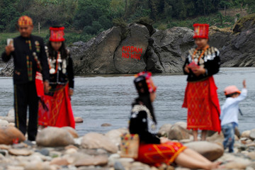 A graffiti on a stone at the confluence of the Mali and Nmai rivers is seen as Ethnic Kachin people pose for photos at Myitsone, outside Myitkyina, capital city of Kachin state, Myanmar