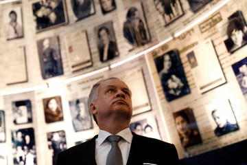 Slovakia's President Andrej Kiska looks at pictures of Jews killed in the Holocaust during a visit to the Hall of Names at Yad Vashem's Holocaust History Museum in Jerusalem