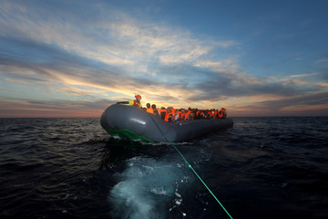 Spanish rescuer, Alberto Agrelo, 31, is seen aboard a plastic raft overcrowded with migrants, as its towed by a rescue RHIB, during a search and rescue operation by Spanish NGO Proactiva Open Arms