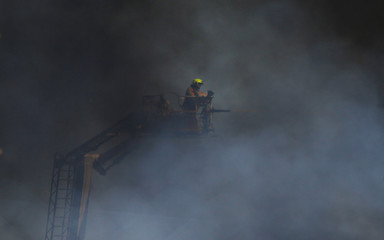 Heat haze from a fire blurs one of more than one hundred firefighters battling a blaze, sending a thick plume of smoke from a recycling plant in Sydney