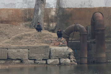 North Koreans squat along the Yalu River in Sinuiju, North Korea, which borders Dandong