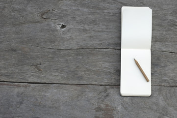 Open blank notepad with empty white pages with a pencil laying on a wooden table