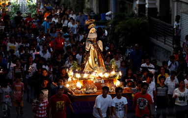 Devotees take part in a Good Friday procession of images of Christ and the Virgin Mary in Mogpog