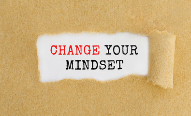 Text Change Your Mindset appearing behind ripped brown paper.