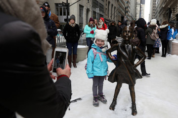 A girl has her picture taken with the 'Fearless Girl' statue which stands in front of Wall Street's Charging Bull statue is seen in New York
